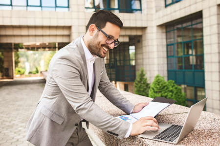 Young businessman using notebook in front of company building. Stockfoto
