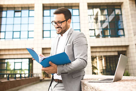Young businessman looking on chart folder in front of the company building.