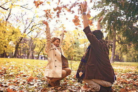 Young smiling couple enjoying fall in the park.