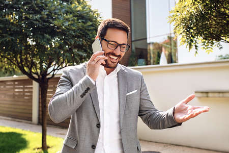 Young businessman using mobile phone in front of company building. Stockfoto