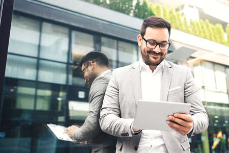 Young businessman using tablet in front of company building.