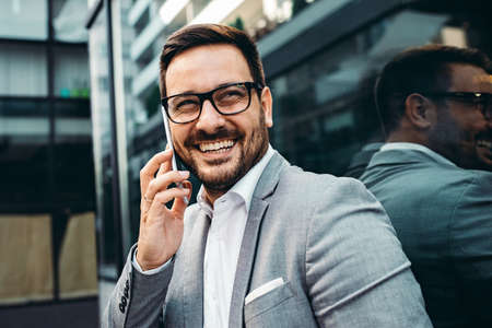 Young smiling businessman in front company building. Stockfoto