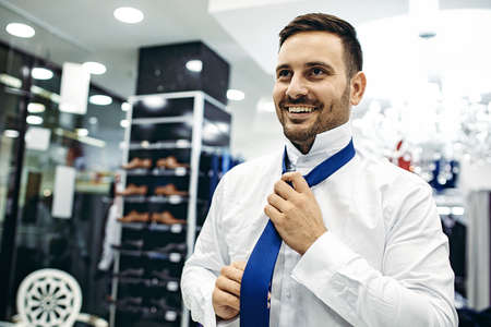 Handsome young man buying clothes in the store. Stockfoto - 132915973