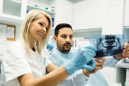 Female dentist and young man patinet in dentist office. Stockfoto