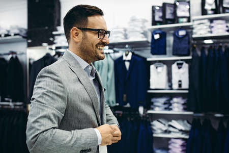 Handsome young man buying clothes in the store. Stockfoto - 132869395