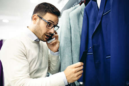 Handsome young man buying clothes in the store.