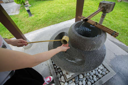 cropped view woman washing hand in a temizuya or the water purification basin. cleansing ritual at shrines in Japan. 免版税图像