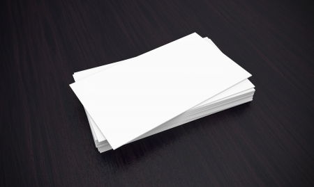 A stack of crispy white business cards on a dark wood desktop  Easy to insert your own company information and logo  Stock Photo