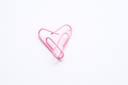 Office romance. Two pink paperclips forming a heart in a symbol of love and romance. Stock Photo