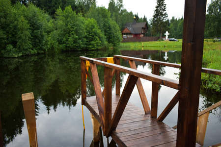 wooden bridge on the shore of the pond