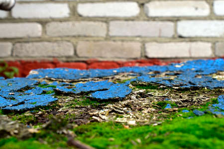 old chipboard with remnants of blue paint against a brick wall Banque d'images