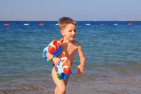 Kid running on the beach photo