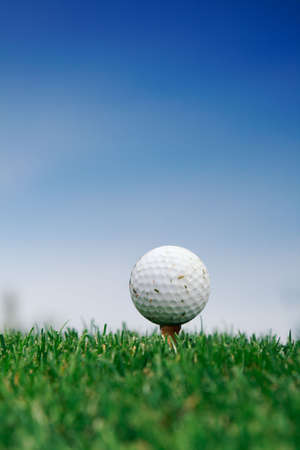 Golf ball on the grass over blue sky