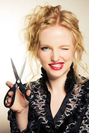 Lovely blond with scissors over grey  Stock Photo - 9947607
