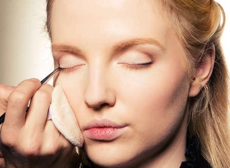 eyelid: Charming young woman applying blusher eyelid