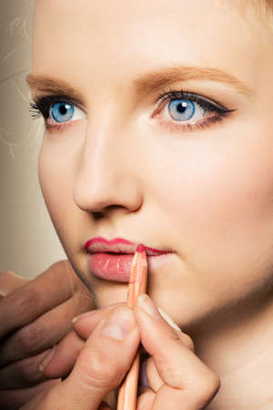 gloss: Portrait of a woman putting on lip liner.