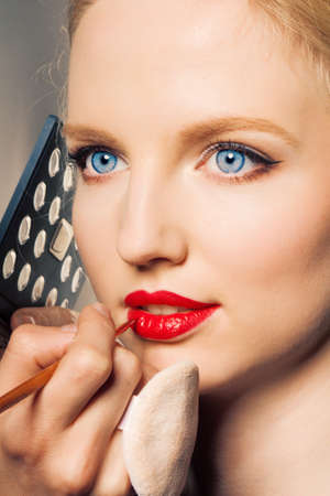 Portrait of a woman putting on lip liner. Stock Photo - 9947234
