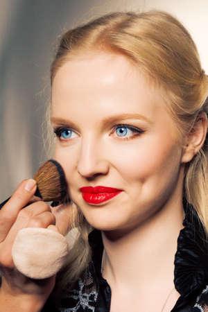 Charming young woman applying blusher eyelid photo