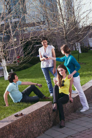 mobile communication: young group communication in park in summer Stock Photo