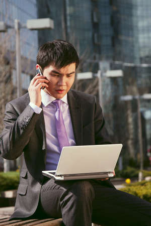 Young businessman sitting and talking on mobile phone  photo