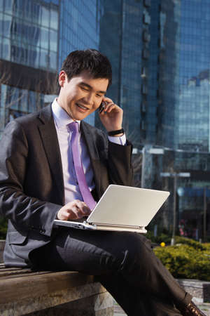 kazakh: Young businessman sitting with laptop. Outdoor.