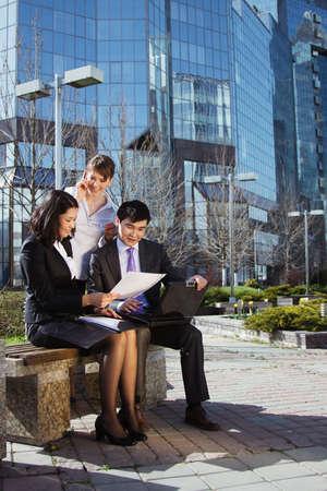 laptop asian: La gente de negocios reuni�n al aire libre delante del edificio de oficinas