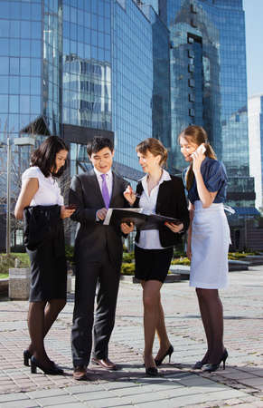 Group of business people meeting outdoor in front of office building Stock Photo