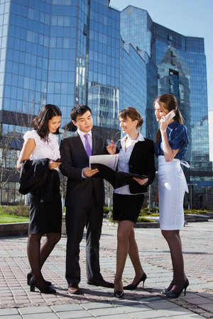 Group of business people meeting outdoor in front of office building photo