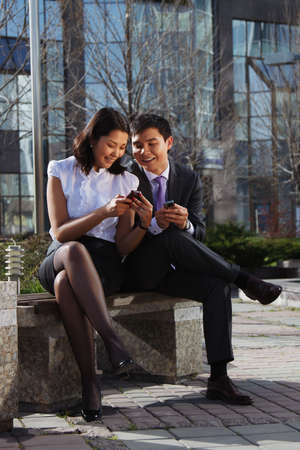 Business couple sitting on the bench chatting with mobile phone Stock Photo
