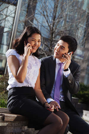 Business couple sitting on the bench chatting with mobile phone Stock Photo - 16799874