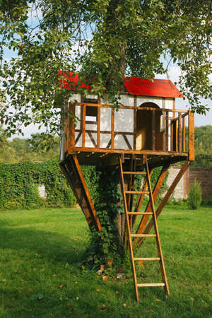 wooden house: Cute small tree house for kids on backyard. German style.