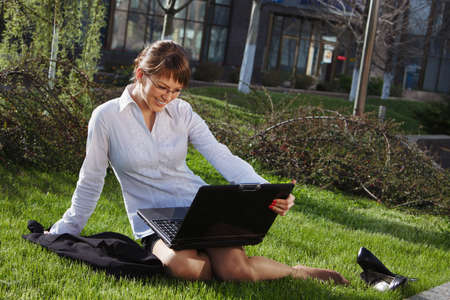 Woman lying on grass with laptop with business building on back photo