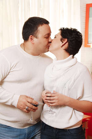 Family in home kitchen drinking wine. Kissing couple photo
