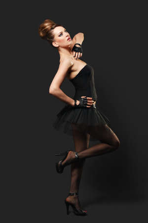 Young and beautiful cabaret dancer over gray background photo