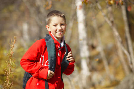 Happy smiling hiker boy with backpack in forest. Dressed in red sweatshirt. photo