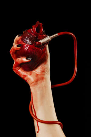 unhappy people: Human heart in hand with pipe, red cable isolated on black