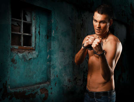 dauntless: horizontal portrait muscular young guy street-fighter, aggression look, over wall Stock Photo