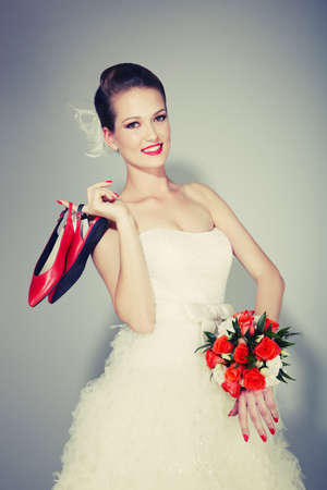Beauty young bride holding red wedding shoes photo