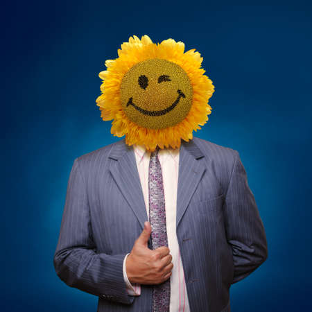 Smiling sunflower head man in suit coat with present thumbs up over blue photo