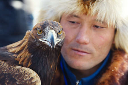 nomadism: NURA, KAZAKHSTAN - FEBRUARY 23: Eagle on mans hand in Nura near Almaty on February 23, 2013 in Nura, Kazakhstan. The traditional event happens yearly and the place becomes as a medieval times city.