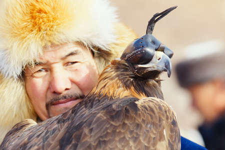 NURA, KAZAKHSTAN - FEBRUARY 23: Eagle on man's hand in Nura near Almaty on February 23, 2013 in Nura, Kazakhstan. The traditional event happens yearly and the place becomes as a medieval times city.
