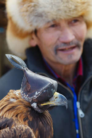 happens: NURA, KAZAKHSTAN - FEBRUARY 23: Eagle on mans hand in Nura near Almaty on February 23, 2013 in Nura, Kazakhstan. The traditional event happens yearly and the place becomes as a medieval times city.