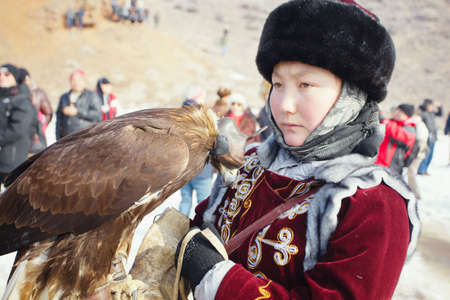 nomadism: NURA, KAZAKHSTAN - FEBRUARY 23: Eagle on girls hand in Nura near Almaty on February 23, 2013 in Nura, Kazakhstan. The traditional event happens yearly and the place becomes as a medieval times city.