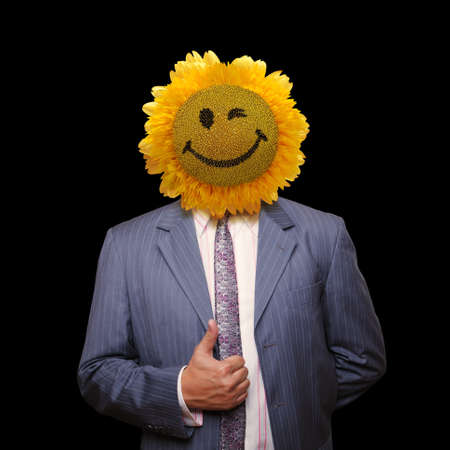 Smiling sunflower head man in suit coat with present thumbs up over black photo