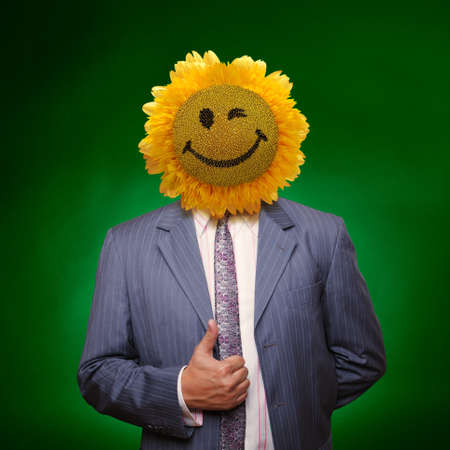 Smiling sunflower head man in suit coat with present thumbs up over green photo