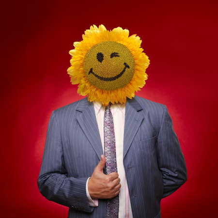 Smiling sunflower head man in suit coat with present thumbs up over red photo