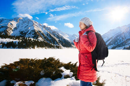 Young woman take a walk on winter mountain slope (Big Almaty Lake, Kazakhstan) photo