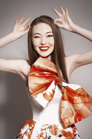 young beautiful asian brunette in gorgeous dress. building horns photo