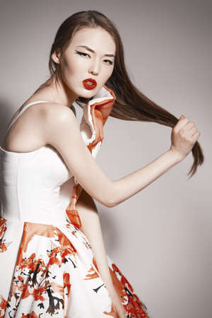 young beautiful asian brunette in gorgeous dress touching hair.  photo