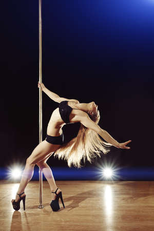Young sexy pole dance woman with fluttering hair performing on stage photo